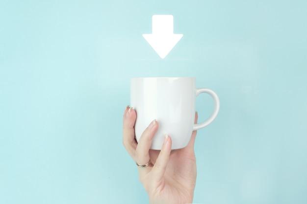Скачать концепцию дня. закройте вверх по утренней кофейной чашке владением руки девушки с иконой знака загрузки на синем фоне.