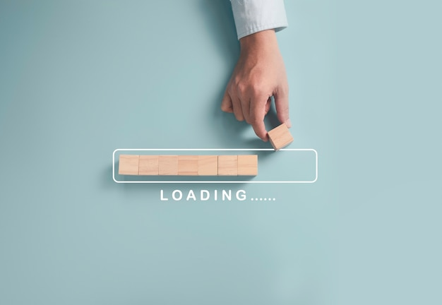 ダウンロードデータ情報とビジネスの進歩的な概念、ビジネスマンが木製の立方体ブロックを置く