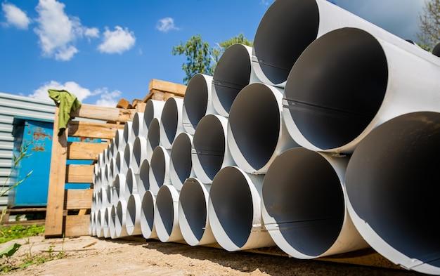 ダウンパイプ倉庫。鋼管、倉庫の屋根排水システムを構築するための部品。ステンレス鋼パイプのスタック。