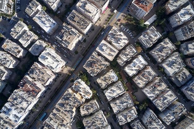 ダウンタウンのインフラストラクチャ、空中ドローンビュー。市内中心部のソーラーパネルと通りのあるアパートの屋根の上面図。