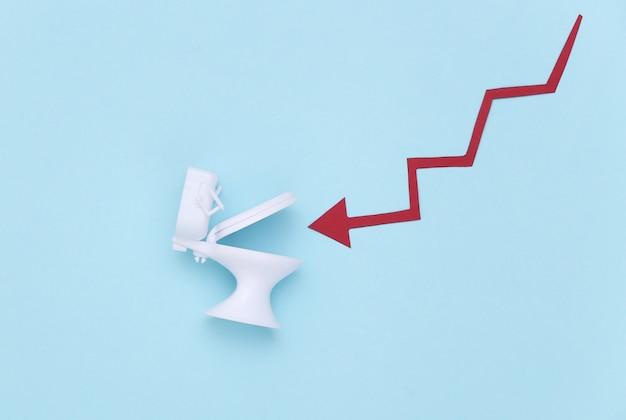파란색 배경에 아래쪽 화살표와 변기. 붕괴, 파산 또는 위기, 경제 개념