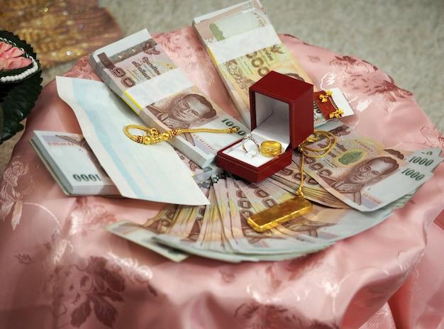 Приданое; золотые монеты и банкноты на розовой атласной ткани для церемонии помолвки тайской свадьбы