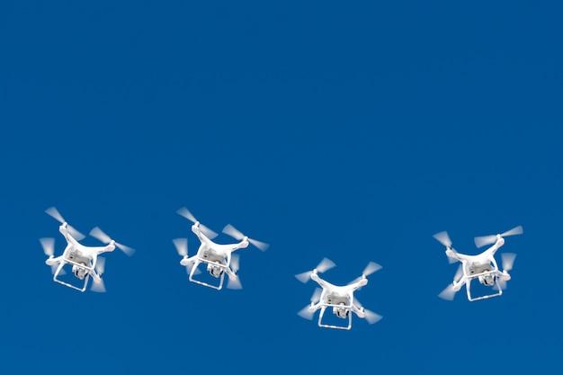 Десятки дронов роятся в голубом небе. дроны quadcopters с цифровой камерой в воздухе над городом.