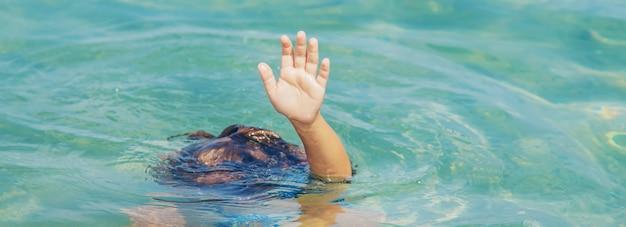 子供は海でdrれています。