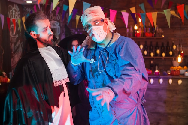 Dracula man looking at his doctor friend while celebrating halloween. scary doctor at halloween party.
