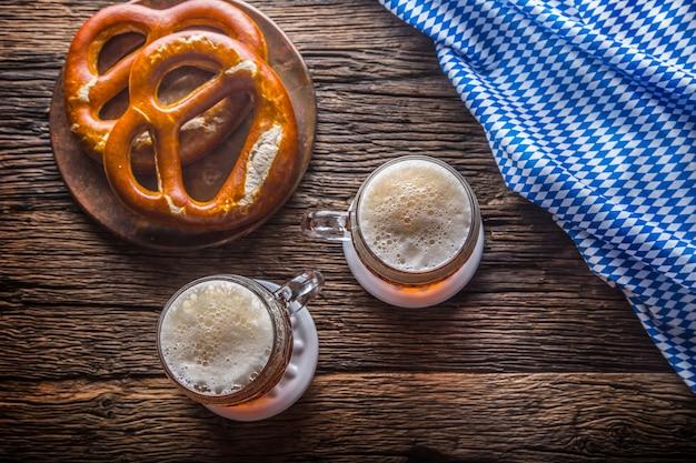 바이에른 축제 옥토버페스트를 위한 전통 제품으로 생맥주 프레첼과 파란색 식탁보