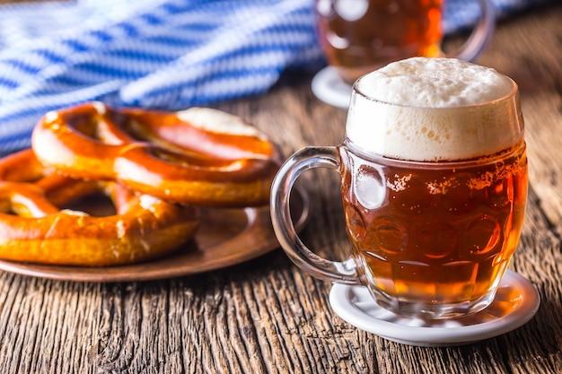 バイエルンフェスティバルオクトーバーフェストの伝統的な製品としてのドラフトビールプレッツェルと青いテーブルクロス Premium写真