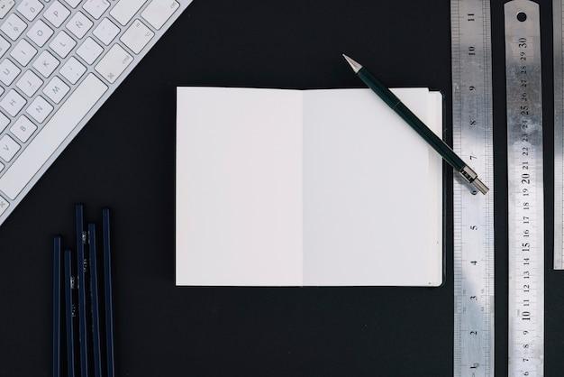 Drafting supplies near notepad and keyboard