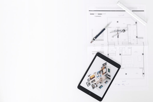 Drafting tools near tablet and blueprints