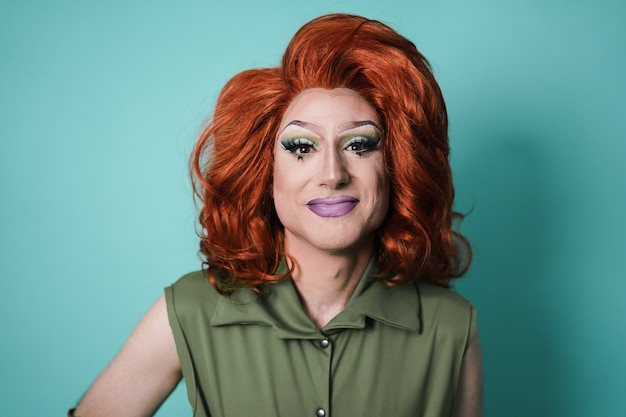 Drag queen smiling on camera with blue background - focus on face