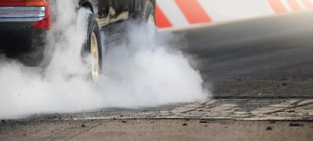 ドラッグレースカーはレースの準備のためにタイヤからゴムを燃やします