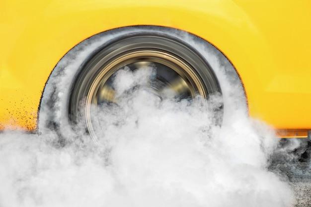 ドラッグレーシングカーはレースに備えてタイヤからゴムを燃やします