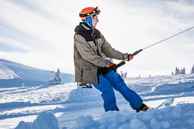 Dragobrat, ukraine -january 11, 2021: man snowboarder using ski yoke to get on the top of the mountains winter sport