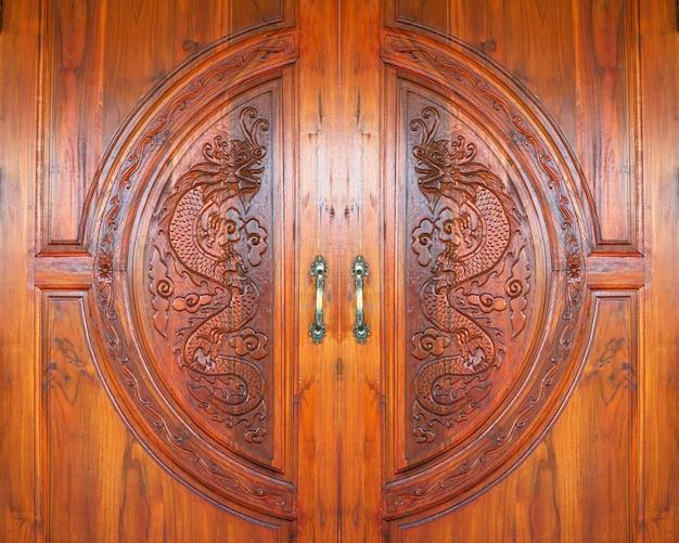 Дракон резной рисунок на деревянной текстуре двери