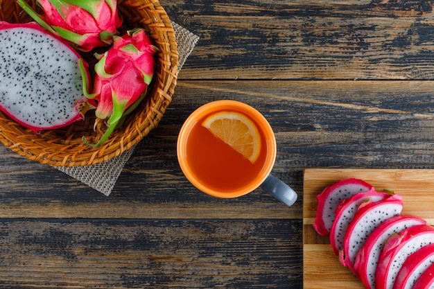 Dragon fruit in a basket with cutting board, tea flat lay on wooden table