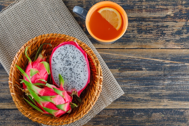 Dragon fruit in a basket with tea top view on wooden table