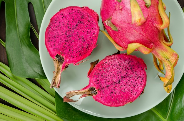 Dragon fruit on a green plate. dark background with palm leaves.