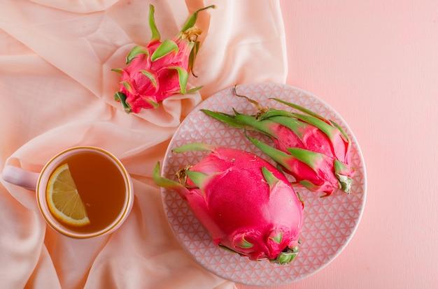 ピンクのテーブルに平らなお茶とプレートのドラゴンフルーツを置く