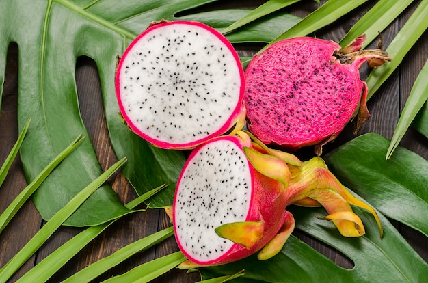 Dragon fruit on the leaves of palm and monster.