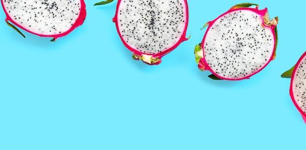 青の背景にドラゴン フルーツまたはピタヤ。おいしいトロピカル エキゾチックなフルーツ。上面図