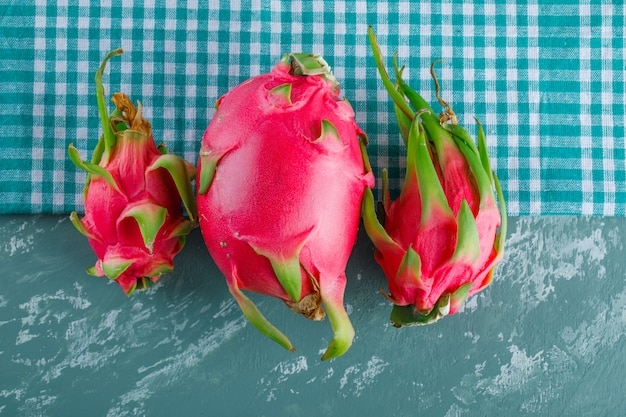 Dragon fruit on plaster and picnic cloth, flat lay.