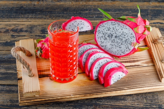 Dragon fruit in a tray with juice high angle view on a wooden table