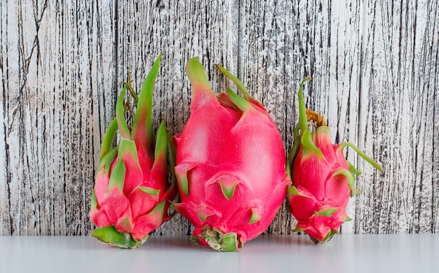 Dragon fruit on  white and wooden table. side view.