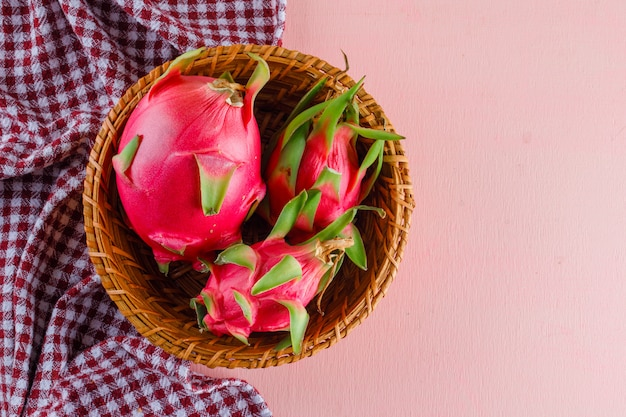 Dragon fruit in a wicker basket on pink and picnic cloth, flat lay.