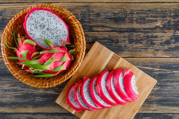 Dragon fruit in a wicker basket on wooden and cutting board. flat lay.