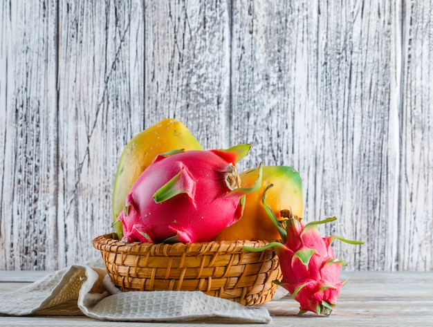 Dragon fruit in a wicker basket on wooden and kitchen towel. side view.