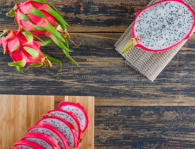 Dragon fruit with cutting board flat lay on wooden table