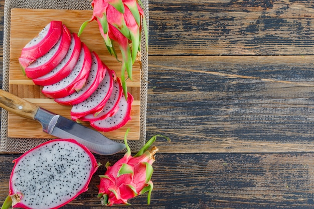 Dragon fruit with cutting board, knife flat lay on wooden table