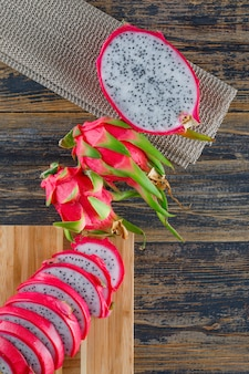 Dragon fruit with cutting board on wooden table, top view.