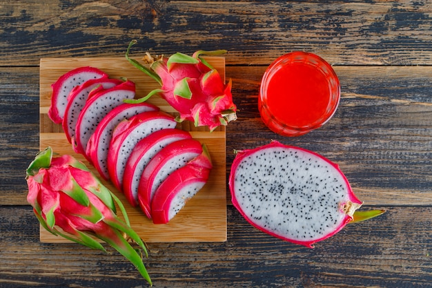 Dragon fruit with juice flat lay on wooden and cutting board