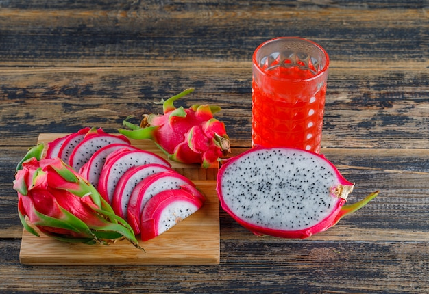 Dragon fruit with juice high angle view on wooden and cutting board