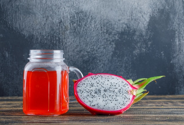 Dragon fruit with juice side view on wooden table and plaster wall