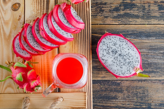 Dragon fruit with juice in a tray on wooden table, flat lay.