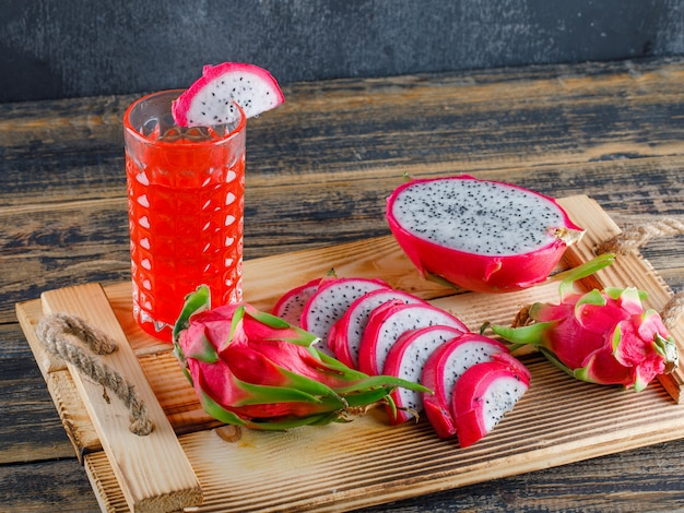 Dragon fruit with juice in a tray on wooden table and plaster wall, high angle view.