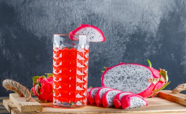 Dragon fruit with juice in a tray on wooden table and plaster wall, side view.