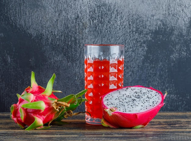 Dragon fruit with juice on wooden table and plaster wall, side view.