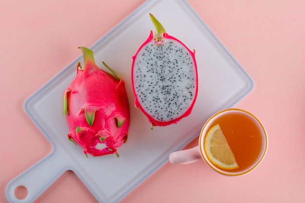 Dragon fruit with tea on pink and cutting board, flat lay.