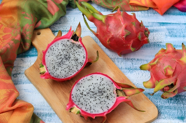 Dragon fruit on wooden board on light blue, top view