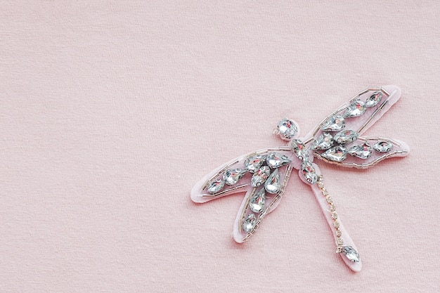 Dragonfly brooch from rhinestones and beads on pink fabric background with copy space. embroidered accessory decor on clothes.