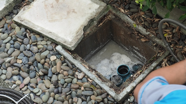 Drain cleaning. plumber repairing clogged grease trap with auger machine. maintenance the sewage system and grease trap by professional plumber. using auger snake to fix and unclog a drain.