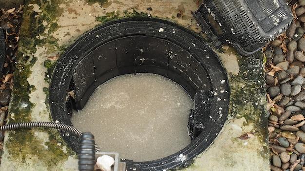 Очистка слива. сантехник ремонтирует забитый жироуловитель с помощью шнековой машины. обслуживание канализации и жироуловителя производится профессиональным сантехником. использование шнековой змеи, чтобы починить и прочистить сток.