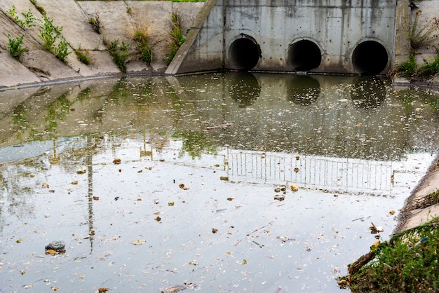 A drain pipe or sewage or sewage discharges waste water into a river.
