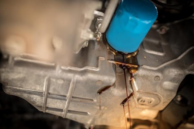 エンジンから古いオイルをドレンプラグを通して排出します。車のエンジンのオイル交換。