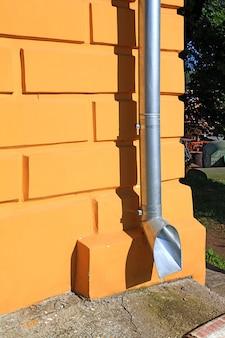 Водосточная труба на оранжевой стене