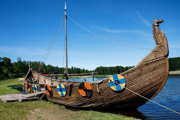 Драккар, лодка викингов, пришвартованная у травянистого берега. круглые щитки на корпусе.