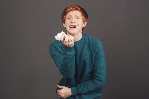 Regina del dramma. ritratto di ragazzo attraente divertente con i capelli rossi in comodo maglione verde vicino finto piangendo e urlando, asciuga le lacrime con il tovagliolo, offeso dal ragazzo al college.